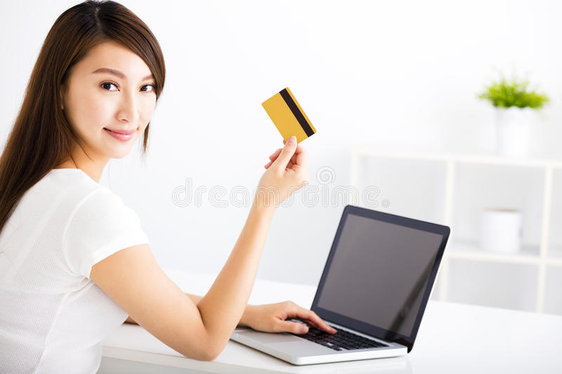 Young woman showing credit card and laptop. Happy young woman showing credit card and laptop stock images