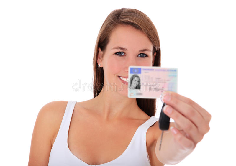Young woman showing drivers license. Attractive young woman showing her new drivers license. All on white background royalty free stock image