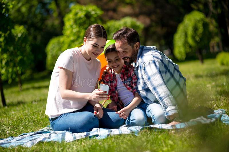 Young Woman Is Showing Photos On Phone To Her Husband And Daughter While Sitting On The Blanket In The Park. stock images