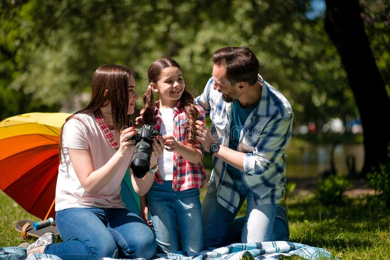 Young Woman Showing Photos To Her Husband And Her Daughter While Sitting On Blanket In The Park. stock photos