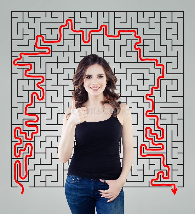 Young woman showing thumb up on maze background. Happy girl planning her life and making decision. stock photography