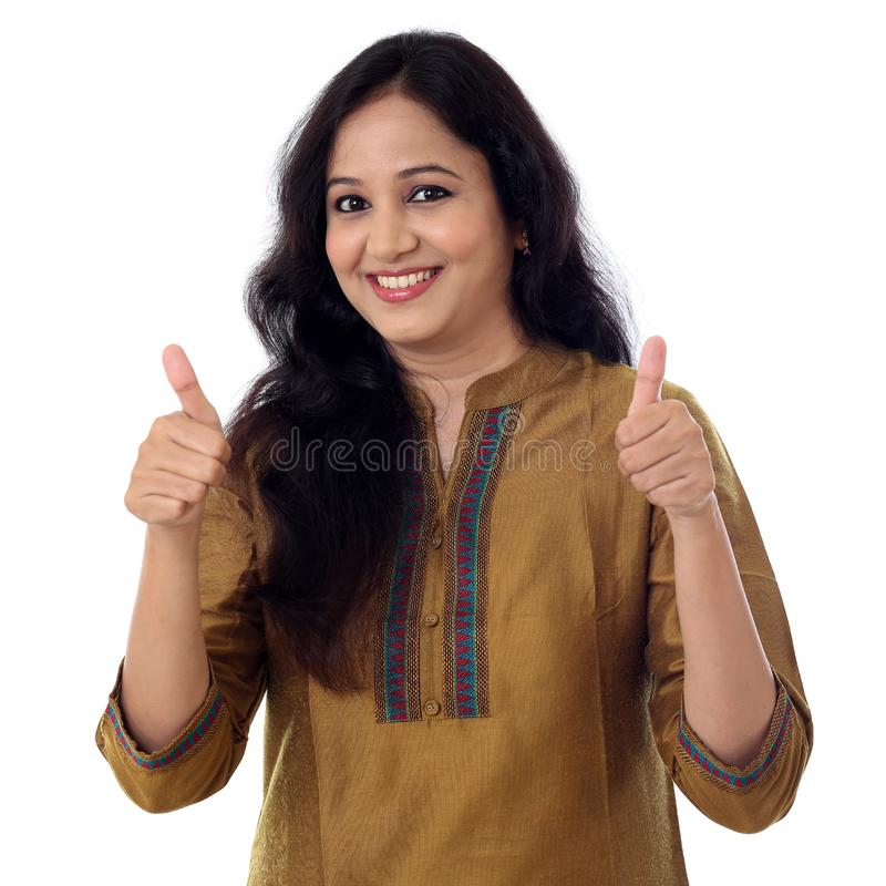 Young woman showing thumbsup gesture against white royalty free stock photos