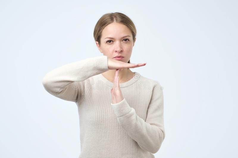 Young woman showing time out gesture with hands isolated on gray wall background. Negative human emotion royalty free stock images