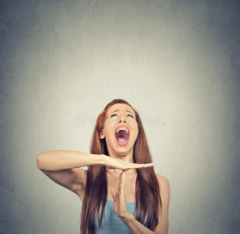 Young woman showing time out hand gesture, frustrated screaming. To stop isolated on grey wall background. Too many things to do. Human emotions face expression royalty free stock photography