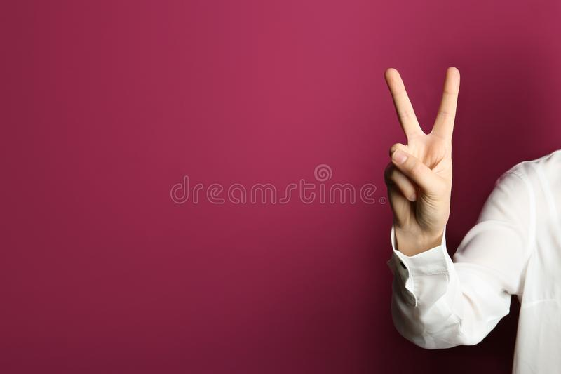 Young woman showing victory gesture on color background. royalty free stock photography