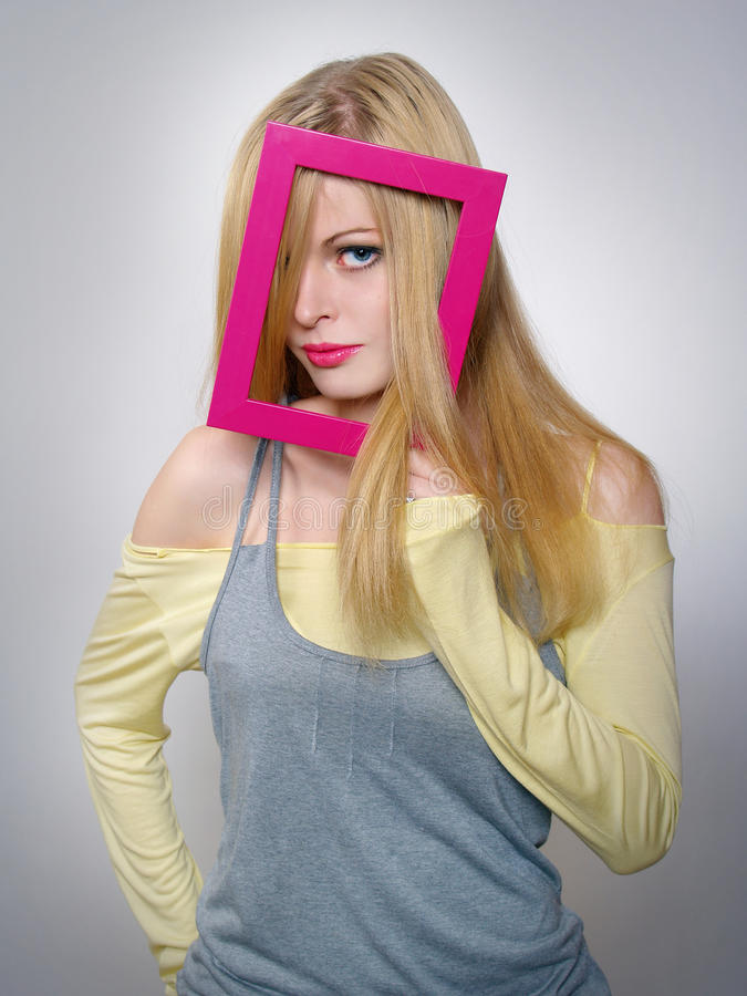 Young woman shows a blond hair through a frame stock photography