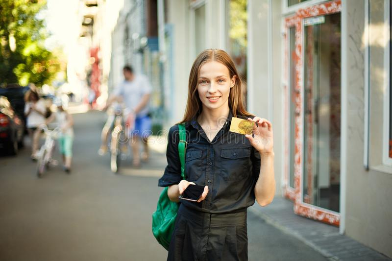 Young woman shows a credit card and holds a mobile phone in the royalty free stock photo
