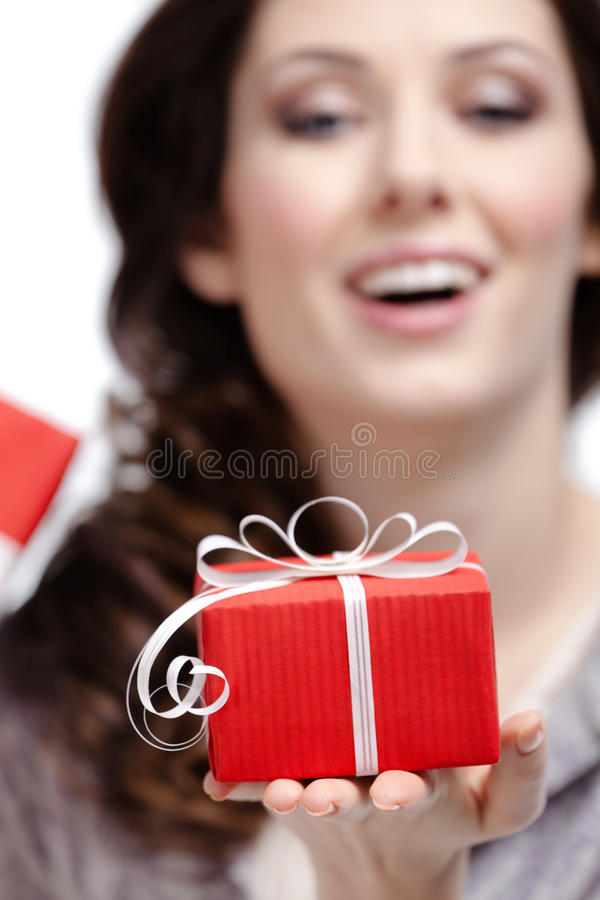 Young woman shows a gift. Wrapped in red paper, isolated on white, close up royalty free stock photos