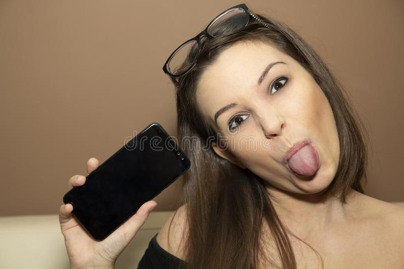 A naughty girl with a smartphone royalty free stock photography