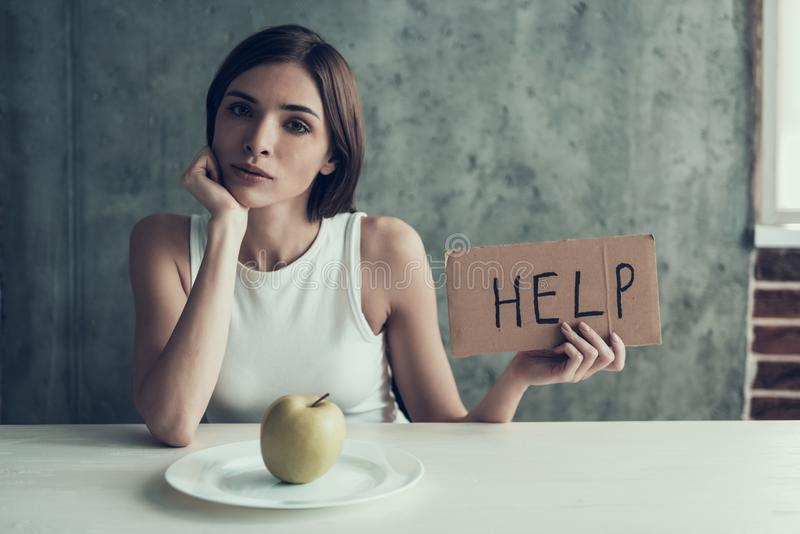 Young Woman with Sign Help and Eating One Apple. stock photo