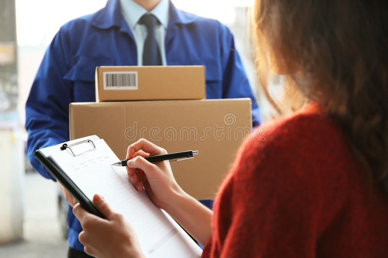 Young woman signing documents after receiving parcels. Young women signing documents after receiving parcels from courier, closeup royalty free stock photography