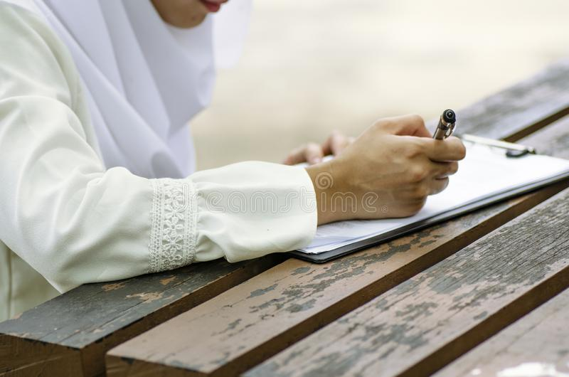 Young woman signing form, sitting on wooden table royalty free stock photos