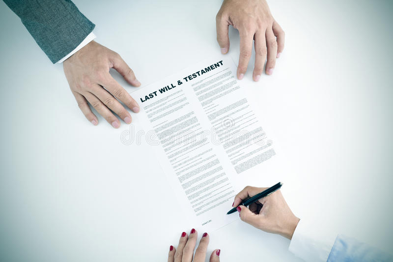 Young woman signing a last will and testament document stock photo