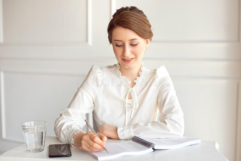 Young woman signs important documents while sitting at her desk in an office. Pretty Caucasian female working in a home royalty free stock images