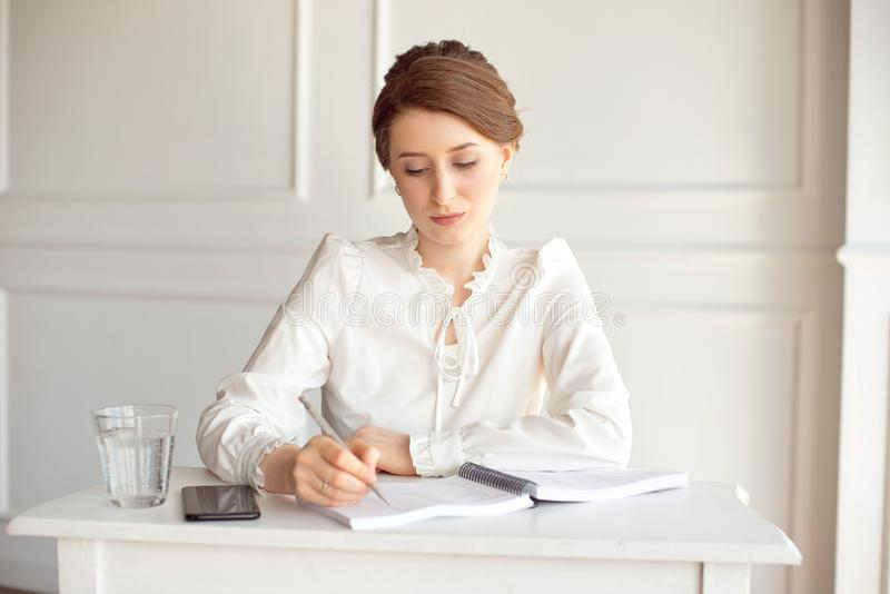 Young woman signs important documents while sitting at her desk in an office. Pretty Caucasian female working in a home stock photography