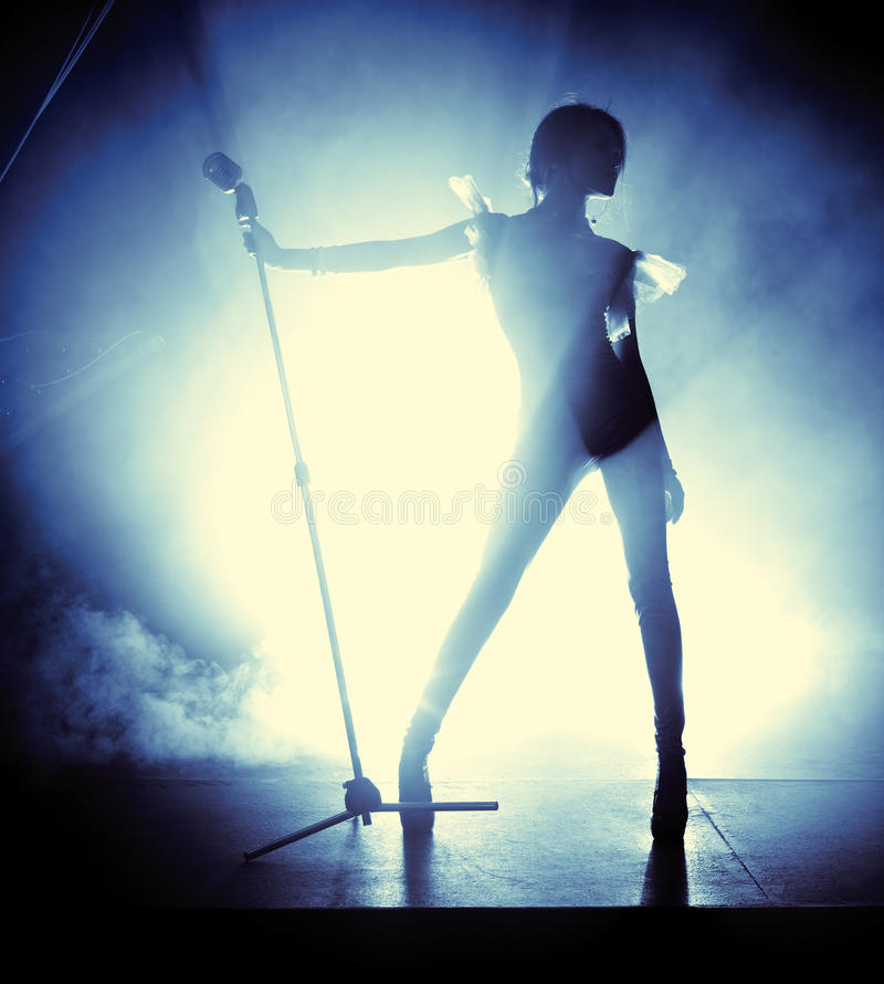 Young woman singer. Contrast silhouette stock image
