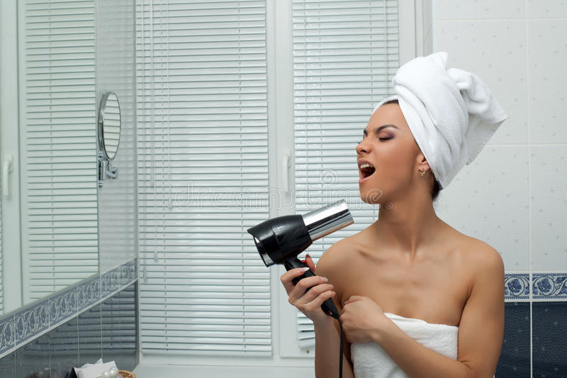 Young woman singing in bathroom stock photos