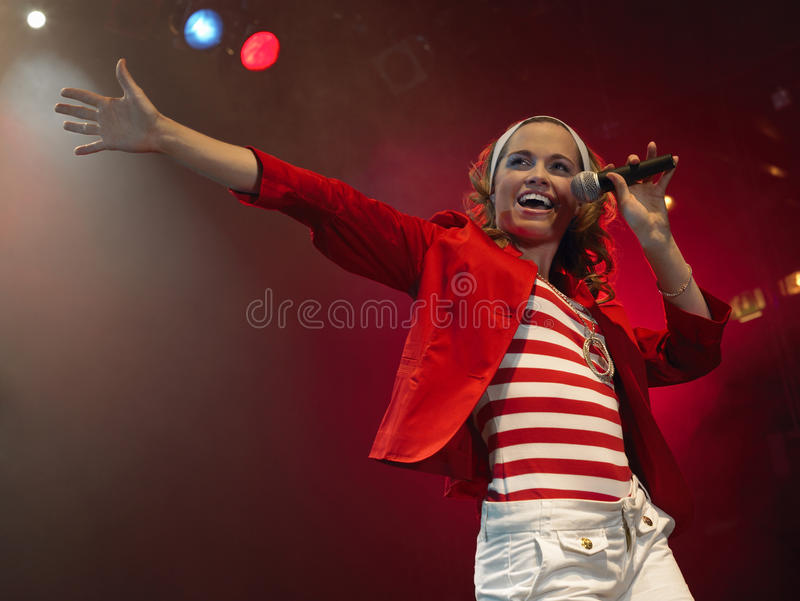 Young Woman Singing Into Microphone stock photography