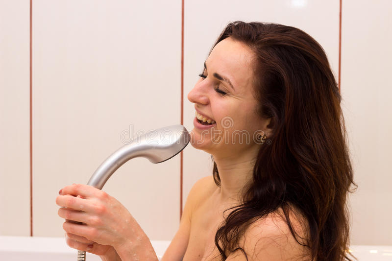 Young woman singing in shower stock images