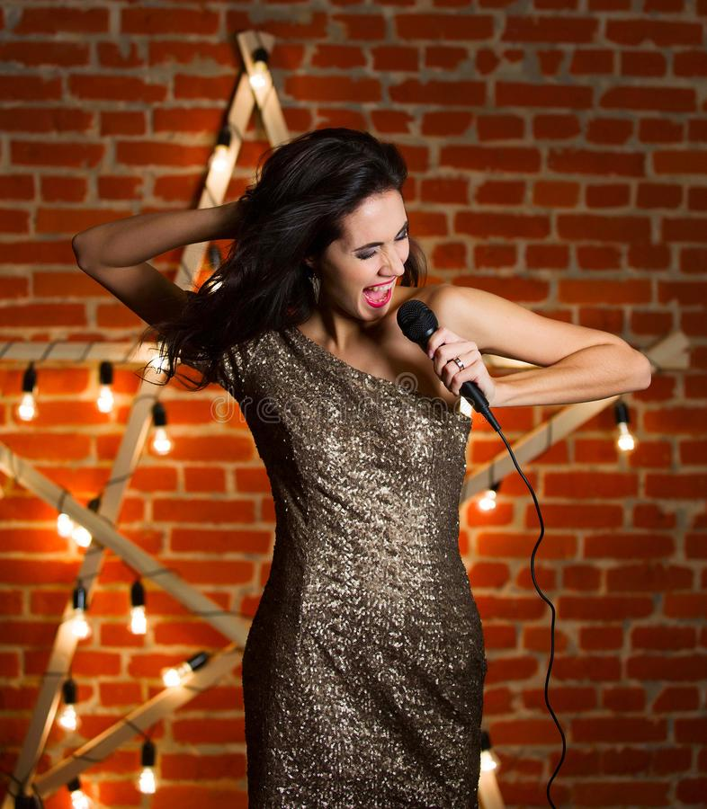 Young beautiful woman singing song over wooden star with bright royalty free stock photos