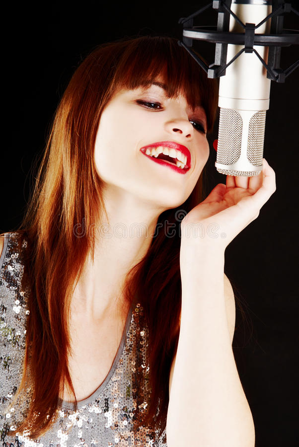 Young woman singing to the microphone in a studio. Face and microphone close-up - Young artist woman recording in a studio royalty free stock images