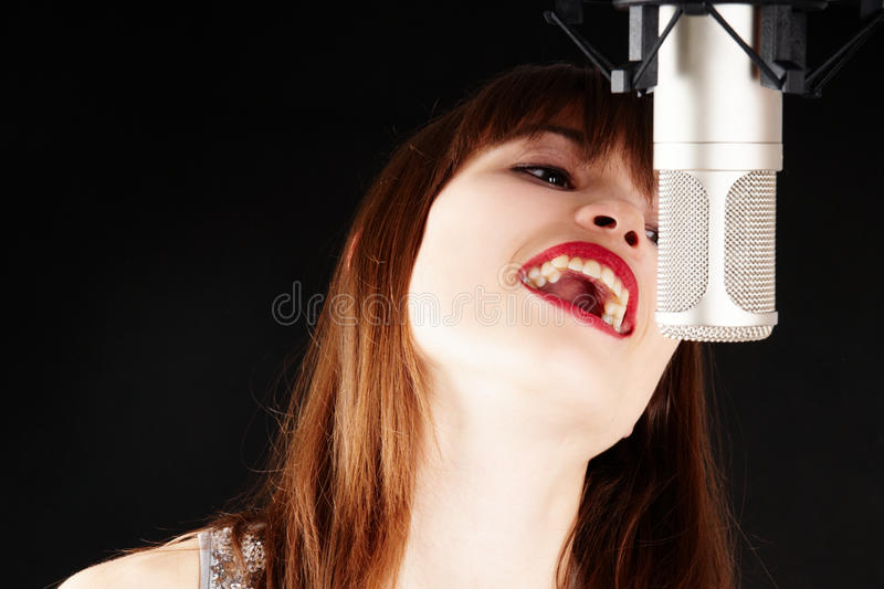 Young woman singing to the microphone in a studio. Face and microphone close-up - Young artist woman recording in a studio royalty free stock photo