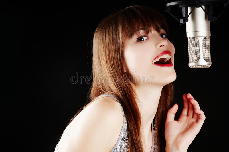 Young woman singing to the microphone in a studio. Face and microphone close-up - Young artist woman recording in a studio stock photos