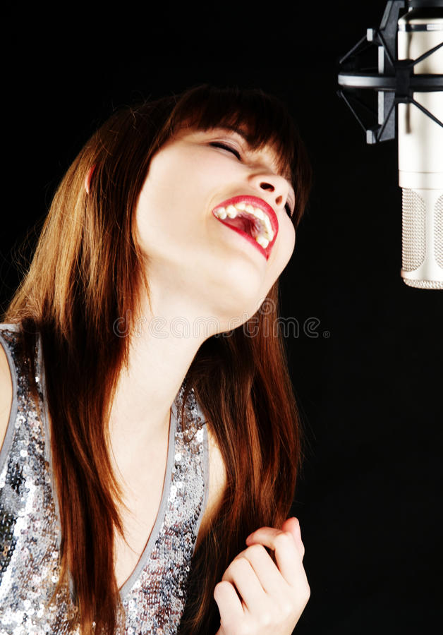 Young woman singing to the microphone in a studio. Face and microphone close-up - Young artist woman recording in a studio stock images
