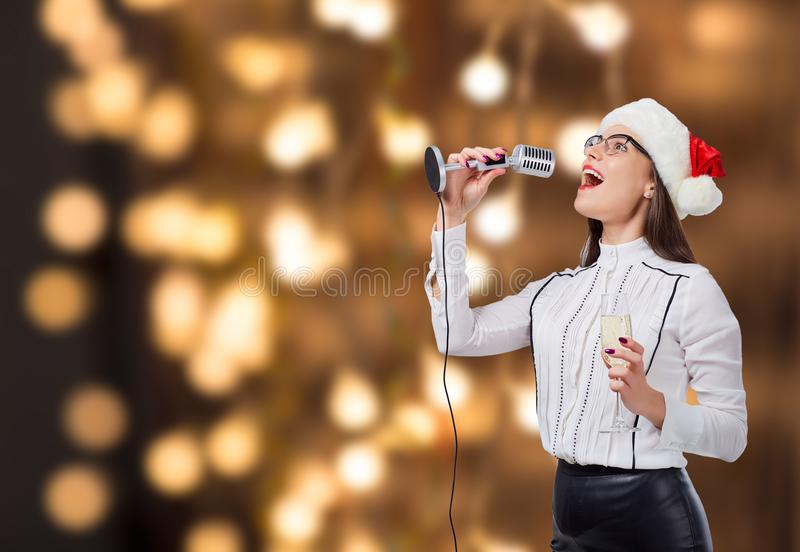 A young woman sings into a karaoke microphone. stock photos