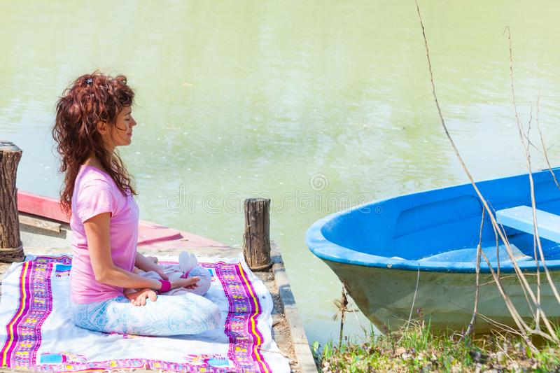 Young woman sit in a meditative yoga position on wooden pontoon on the lake hold magnolia flower stock photo
