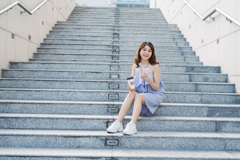 Young woman sit and using smart phone at outdoor stair,  Lifestyle of modern female stock image