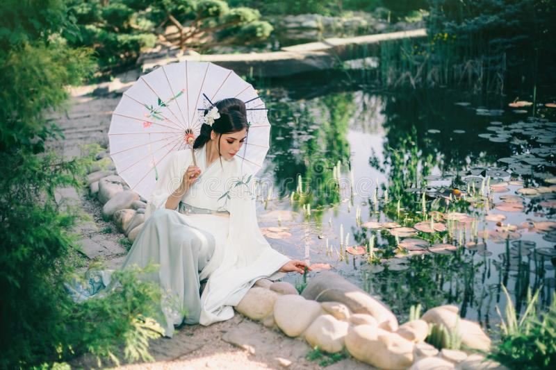 A young woman sits at a beautiful decorative lake, she is dressed in a tender Japanese kimono of ivory, a mint skirt stock image