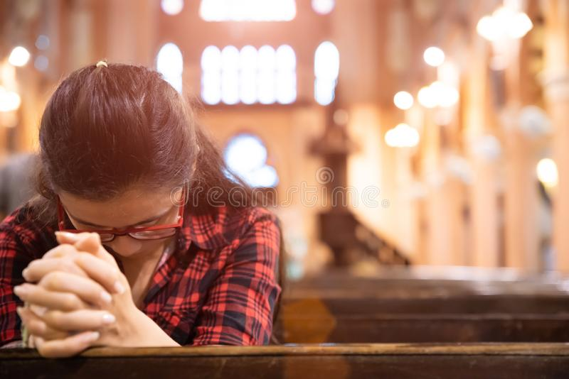 Young woman sits on a bench in the church and prays to God. Hands folded in prayer concept for faith royalty free stock images