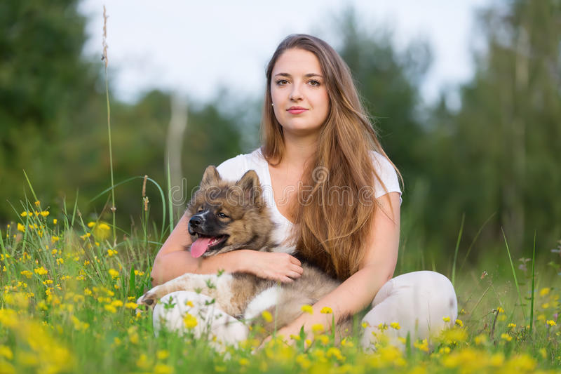Young woman sits with an Elo puppy in the grass royalty free stock photos