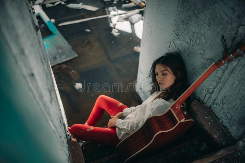 A young woman sits with guitar inside of old abandoned ship stock photos