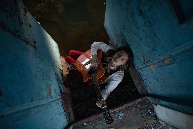 A young woman sits and plays guitar inside of old abandoned ship stock images
