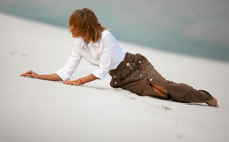 Young woman sits on sand in desert and pensively looks aside. royalty free stock photography