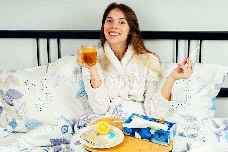 Young woman sitting alone on the bed and golding a cup of tea in one hand and a thermometer in another stock photos