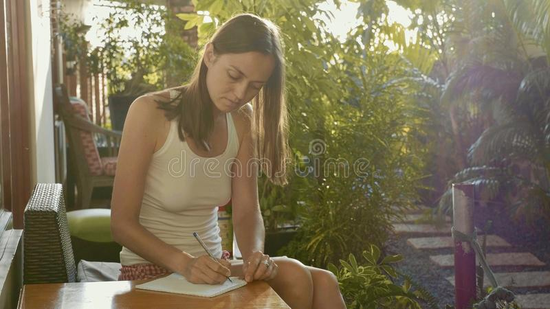 Young woman sitting at balcony in sunlight and writing in diary by ballpen. With garden on the background stock photo