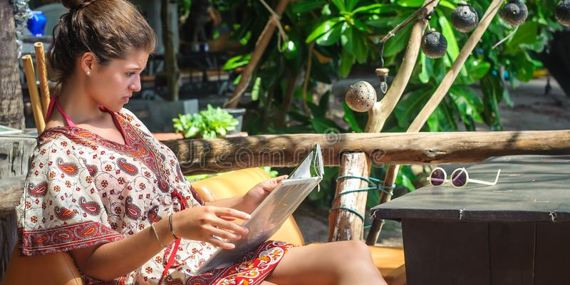 Young woman sitting in bamboo beach bar, looking at menu. Summer holiday trip royalty free stock images