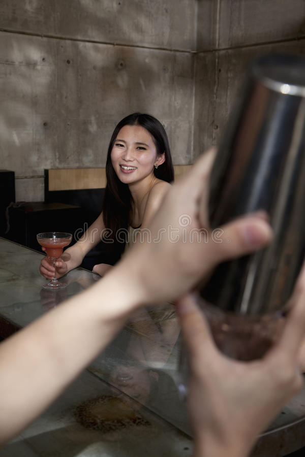 Young woman sitting at bar counter observing bartender stock image