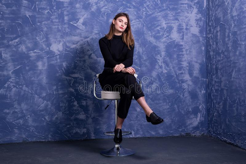 A young woman is sitting on a bar stool against the background of a blue wall, free space stock image