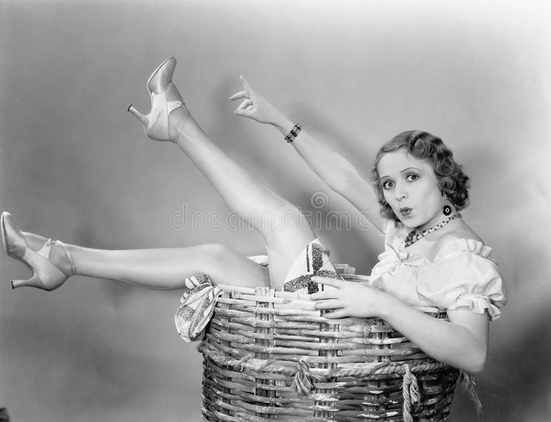 Young woman sitting in a basket looking surprised stock images