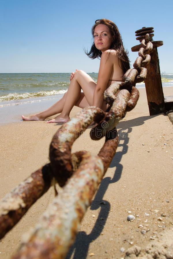 Young woman sitting at the beach stock photo