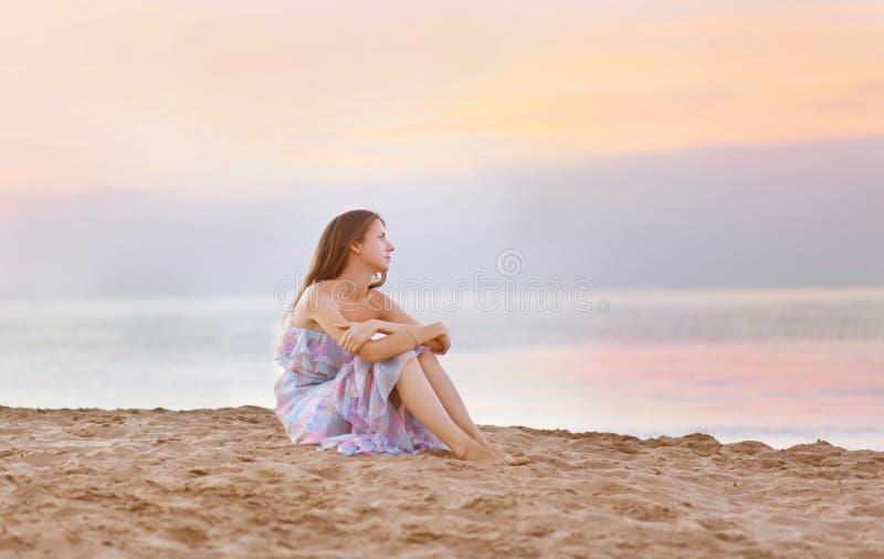 Young woman sitting on the beach at coast enjoying sea royalty free stock image