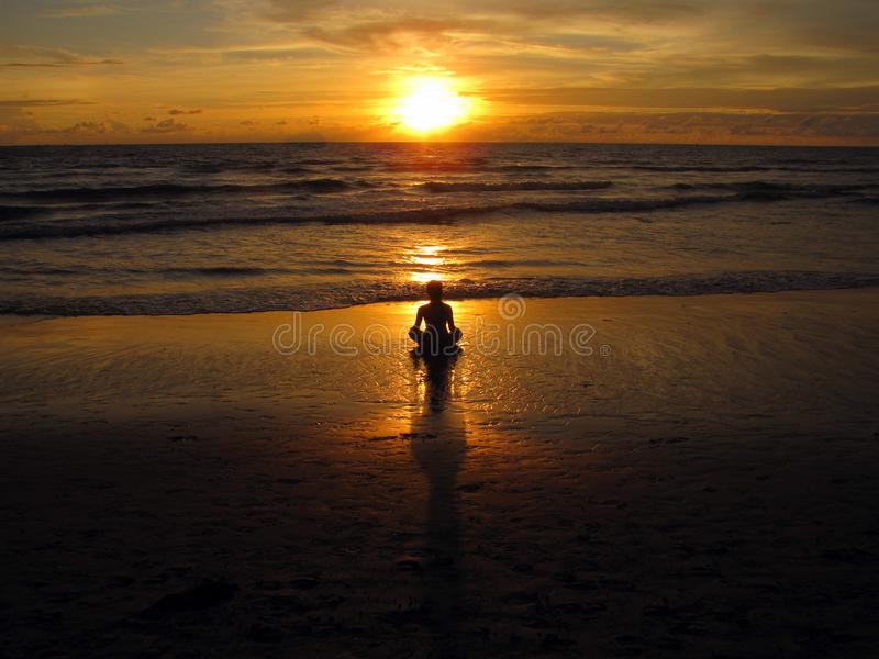 Young woman sitting on the beach, silhouette at sunset. Young woman practicing yoga outdoors. Harmony and meditation concept. Healthy lifestyle. meditate in stock images