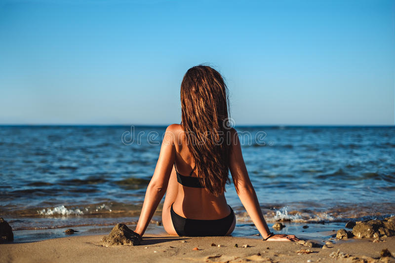 Young woman sitting on the beach and watching the sea stock photos