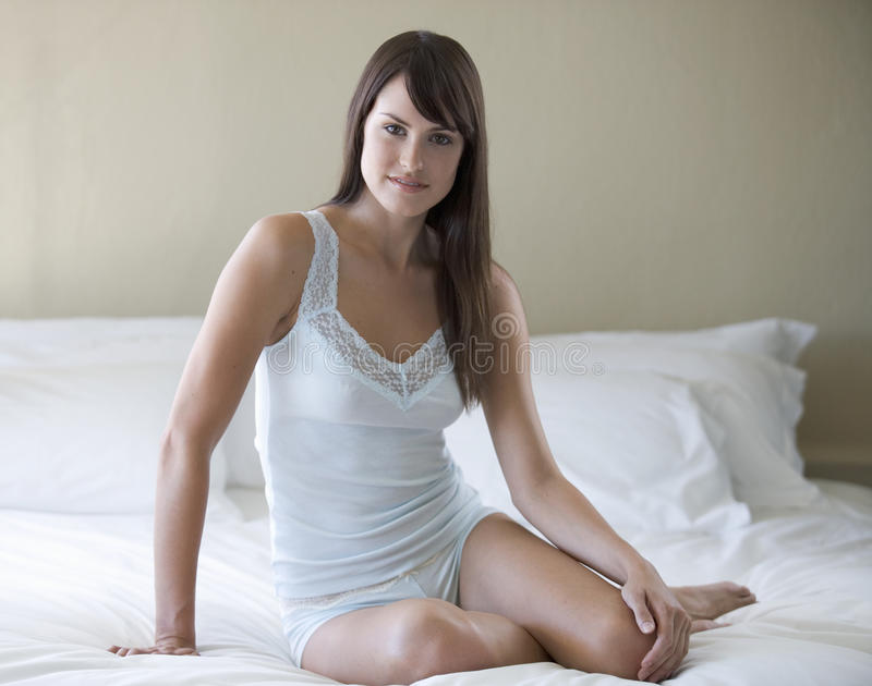A young woman sitting on a bed stock photos