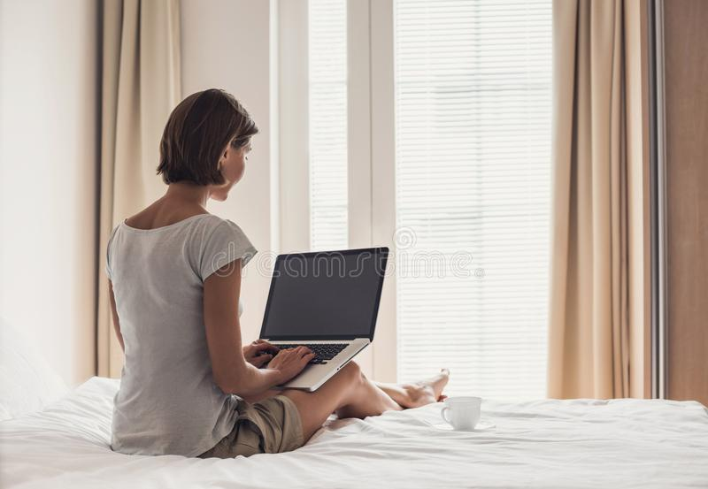 Young woman sitting on the bed at home and using laptop computer stock image