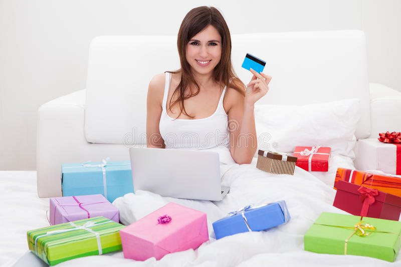 Young Woman Shopping Online. Young Woman Sitting On Bed And Shopping Online stock images